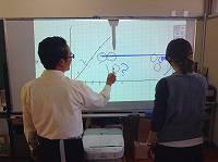 プロジェクター単体で書き込みをする様子。超短焦点プロジェクターなので投影面の間近に設置されています。