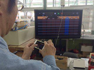 iPod Touch で GarageBand のスマートギターを操作する様子が地デジテレビに映し出されています。
